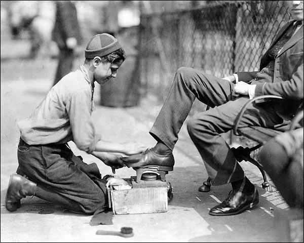 boy shining mans shoe
