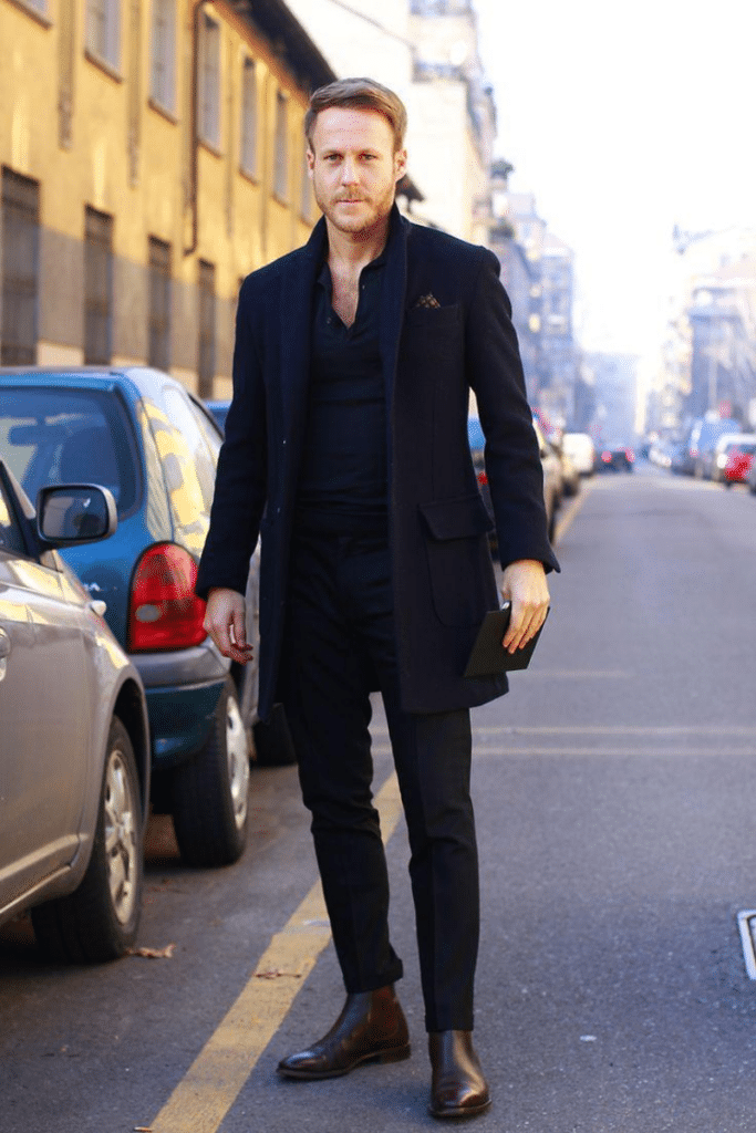 man wearing all black outfit that includes chelsea boots