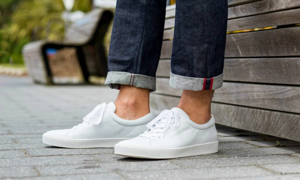 man wearing white trainers and jeans